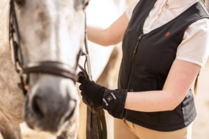Woman wearing Blaze Wear Activie Gilet and Blaze Wear Traveller Gloves whilst caring for her horse